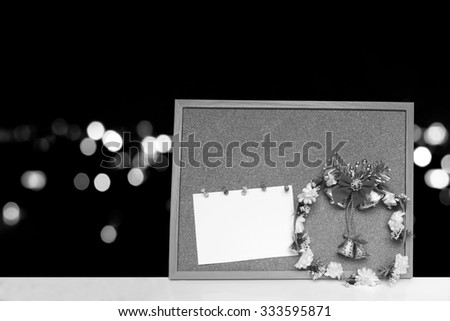 Wreath and card on cork board with  blur bokeh light in city background ,black and white tone - stock photo