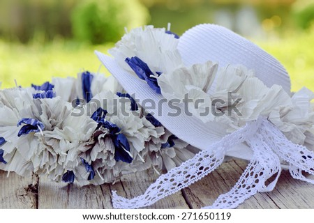 Wreath and hat on a table outside - stock photo