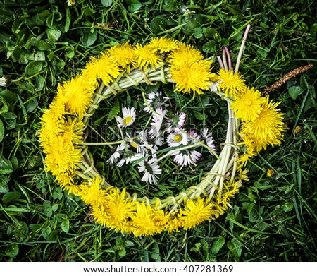 Wreath of dandelions with ox-eye daisies in the green grass. Seasonal natural scene. - stock photo