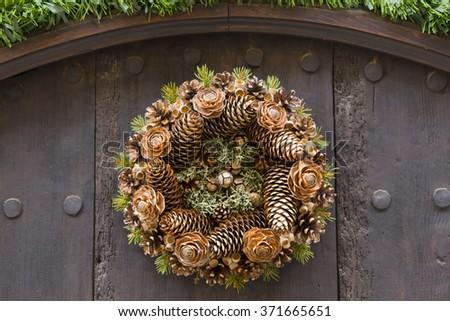 Wreath with pinecones, hanging in a wooden door - stock photo