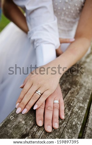 Wreathed hands of lovers. Hands of spouses being in the amorous touch on the wooden railing of stairs