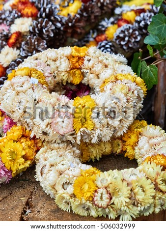 Wreaths and pots decorate the entrance in front of a flower shop.