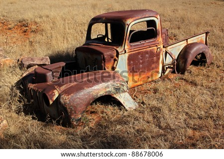 Wreck of a rusty old pickup truck out in the field - stock photo