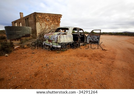Wrecked abandoned car alongside remains of ruined 19th century stone house.  Silverton, outback New South Wales, Australia.