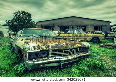Wrecked american cars at an oldtimer scrapyard, HDR processing - stock photo