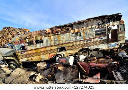 Wrecked bus in a junkyard - stock photo