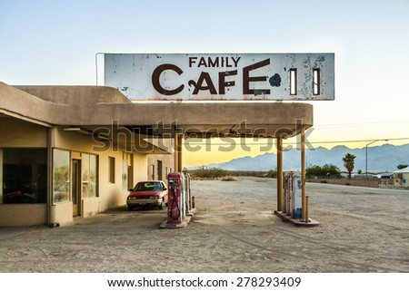 wrecked car at an abandoned petrol station in the desert village of Desert Center in sunset - stock photo