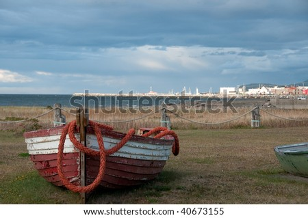 wrecked fishing boat with fishing village in background, scenic view before a storm. Mont Ste Anne ,Gaspesie, Canada - stock photo