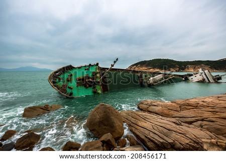 Wrecked ship along the rocky coast - stock photo
