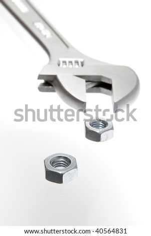 Wrench and metal nuts on white background