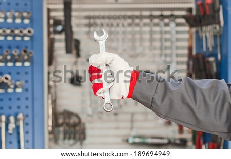 Wrench in hand against the cabinet with tools. - stock photo
