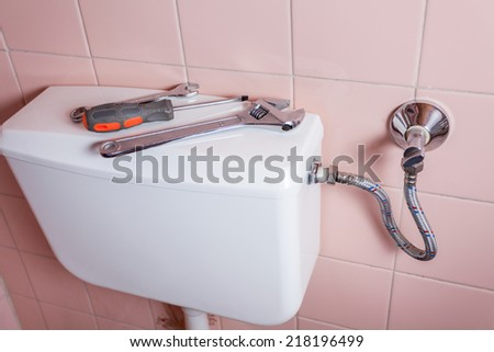 Wrench spanner and screwdiver lying on a toilet - stock photo