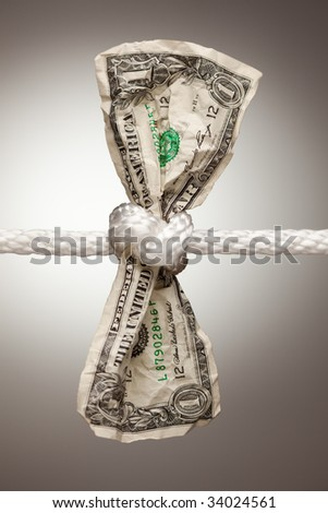 Wrinkled American Dollar Tied Up in Rope. - stock photo