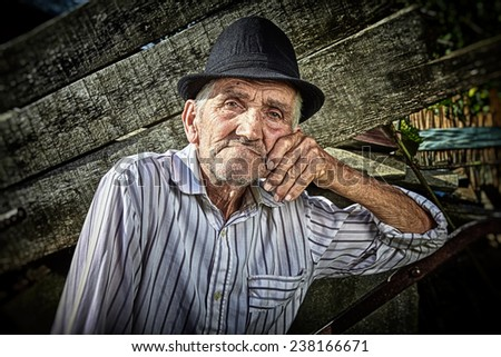 Wrinkled and expressive old farmer in the yard. Close-up. - stock photo