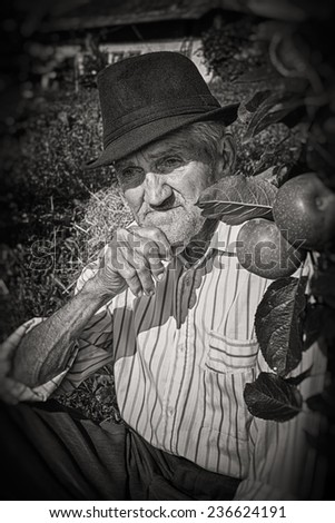 Wrinkled and expressive old farmer leaning on an apple tree in the yard. Black and white picture. - stock photo