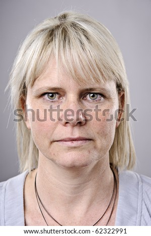wrinkled blonde woman poses for a portrait in studio