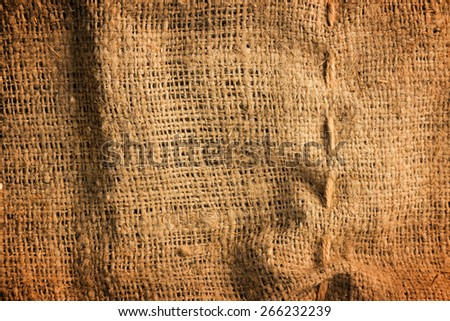 Wrinkled brown burlap fabric background texture. - stock photo