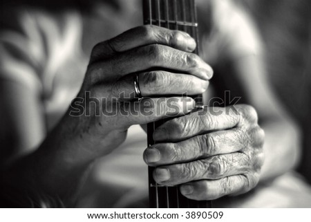 wrinkled hands and guitar