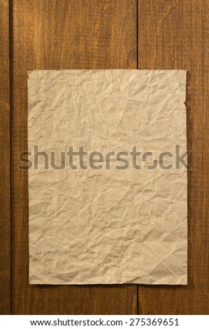 wrinkled note paper on wooden background