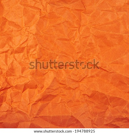 Wrinkled orange paper fragment as a background texture - stock photo