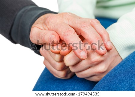 Wrinkled reassuring hand on young anxious hands - stock photo