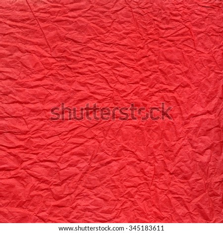 Wrinkled scarlet red paper texture. Crushed surface background.
