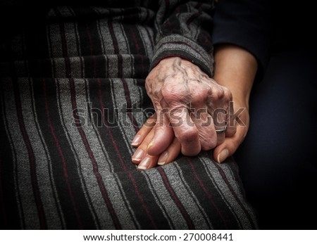 Wrinkled skin hand of aged woman holding hand of young lady - stock photo