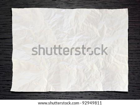 Wrinkled White paper on dark wood background - stock photo