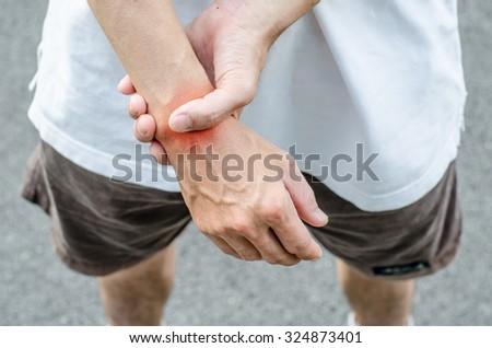 Wrist pain. Male holding hand to spot of wrist pain. - stock photo
