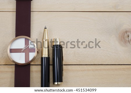 wrist watch and pen on wooden background - stock photo