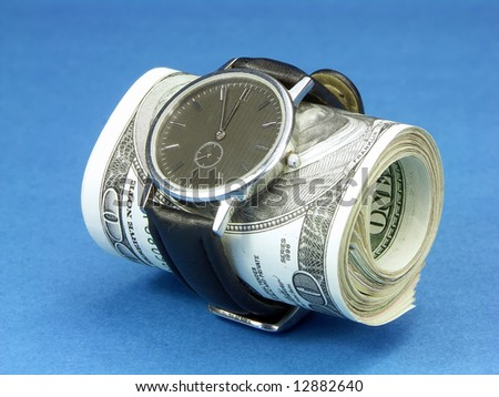 Wrist watch wrapped around a roll of 100 us dollar banknotes over blue background - stock photo
