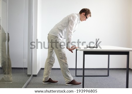 wrists exercise during office work - standing man reading at tablet in his office  - stock photo