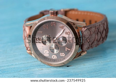Wristwatch on old wooden table - stock photo