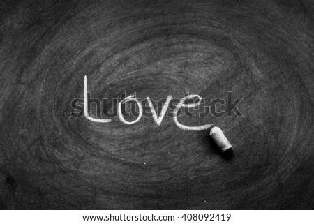 "write a chalk ""Love"" on a black board - stock photo"