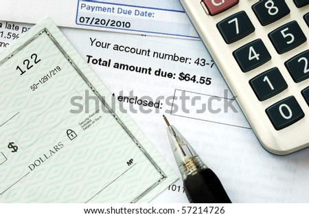 Write a check to pay the bills on time - stock photo