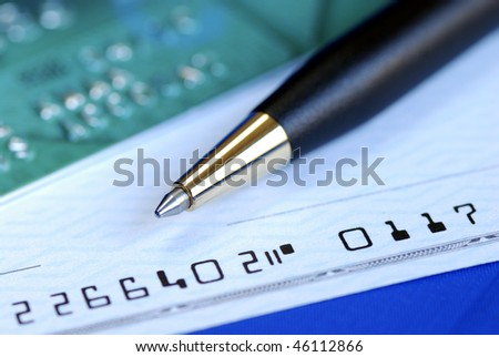Write a check to pay the credit card bill isolated on blue - stock photo