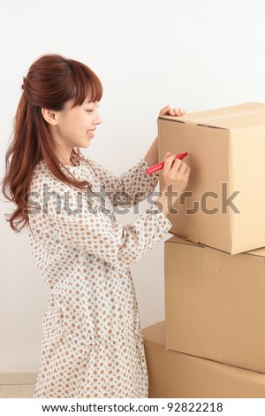 Write a young Asian woman in a cardboard box - stock photo