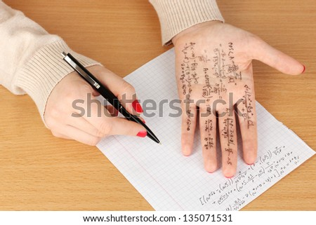 Write cheat sheet on hand on wooden table close-up - stock photo