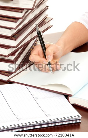 Writer business person hand with pen signing document. On the table stack of books organizer notebook on white background - stock photo