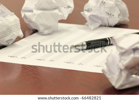 Writer's Block: Blank staff paper, mechanical pencil, and crumbled balls of paper scattered on a wooden desk. - stock photo