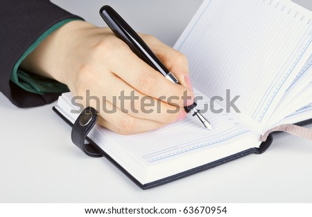 Writes in diary - stock photo
