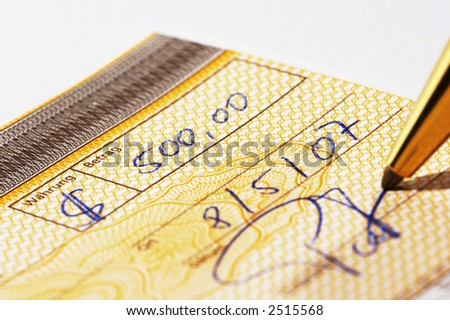 Writing a bank check with a pen - stock photo