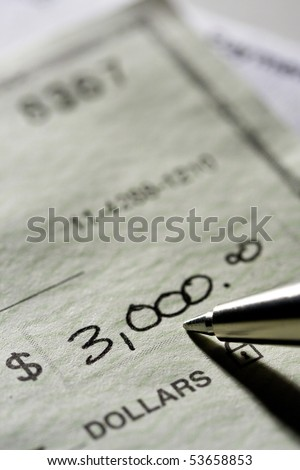 Writing a check and pay the bill.  Shot with shallow depth of field. - stock photo