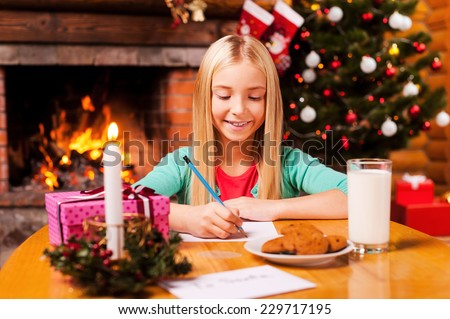 Writing a letter to Santa. Cute little girl writing a letter to Santa Claus while sitting at home with Christmas tree and fireplace in the background - stock photo