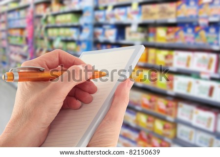 Writing a Shopping List in the Supermarket - stock photo