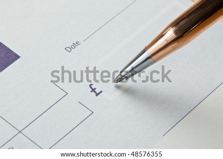 Writing a UK Sterling check with a gold pen on a blank light blue check