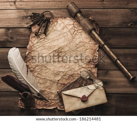 Writing accessories and spyglass  on a vintage blank paper  - stock photo