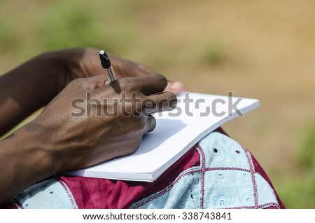 Writing Activity - African Schoolgirl Writing a Letter Outdoors - stock photo