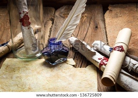 Writing ancient feather letter and send it in a bottle - stock photo