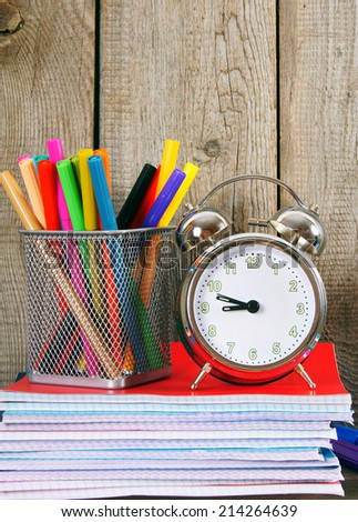 Writing-books, an alarm clock and school tools on a wooden shelf. On a wooden background.